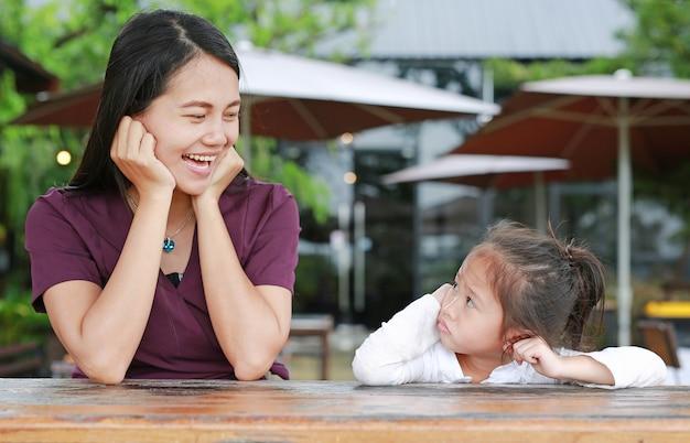 Feliz linda mãe asiática falando com a filha na mesa de madeira no restau ao ar livre
