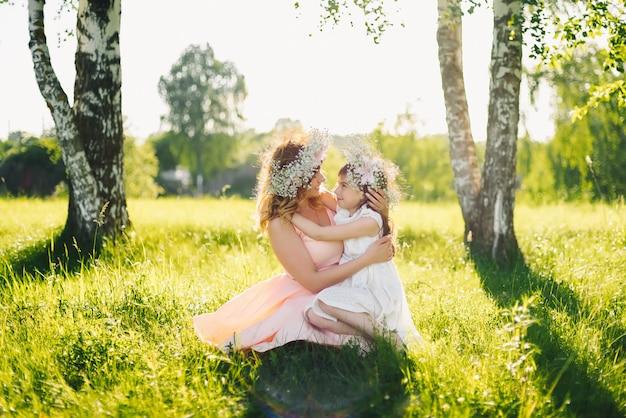 Feliz linda mãe com uma filha de aparência caucasiana, abraçando no prado