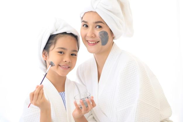 Feliz linda mãe e filha em um roupão de banho branco aplicando máscara facial no quarto, família e conceito de beleza