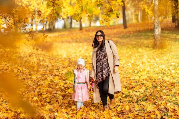Feliz linda mãe mulher com sua filha em roupas da moda caminhando no parque outono com folhagem amarela ao ar livre