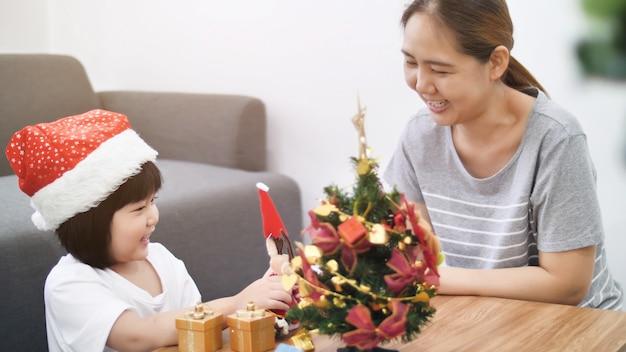 Feliz linda menina asiática decorando ornamento na árvore de natal com a mãe dela