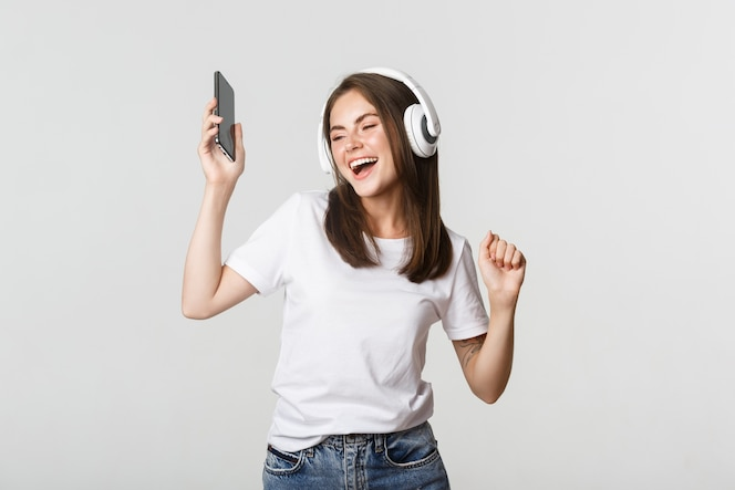 Feliz linda menina morena dançando e ouvindo música em fones de ouvido sem fio, segurando o smartphone.
