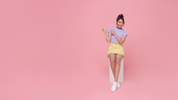 Feliz linda mulher adolescente asiática sentada na cadeira e as mãos apontando no fundo rosa com espaço de cópia. fundo panorâmico.