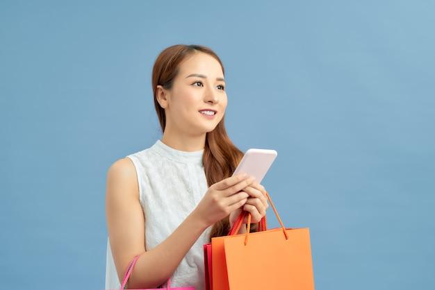 Feliz linda mulher asiática carregando sacolas de compras em fundo azul isolado, conceito de venda de verão.