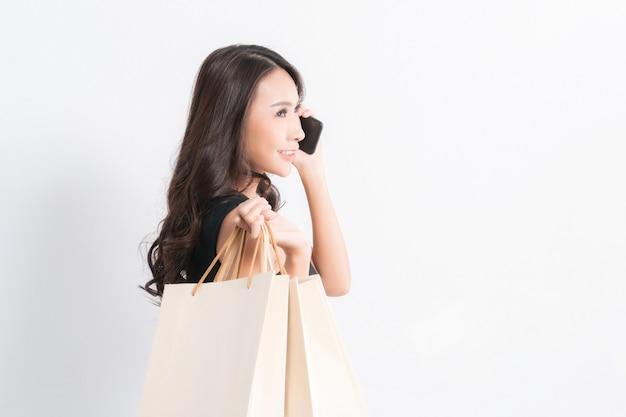 Feliz linda mulher asiática negra de cabelos compridos, vestindo uma camisa preta, jeans usando um telefone celular e carregando sacolas de compras no fundo cinza isolado,