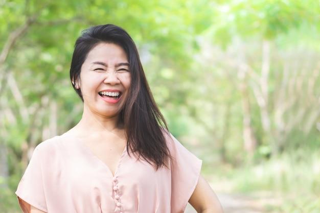 Feliz linda mulher asiática rindo ao ar livre