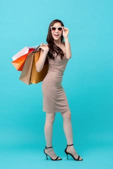 Feliz linda mulher asiática shopaholic carregando sacolas de compras