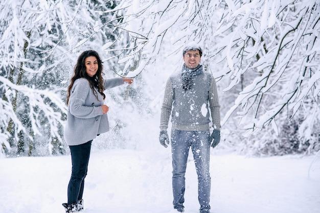 Feliz linda mulher grávida em roupas quentes jogando neve no marido