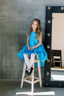 Feliz linda surpresa linda encantadora pequena menina com sorriso, ela está usando vestido azul, sentado no banquinho, isolado na parede cinza brilhante, copyspace