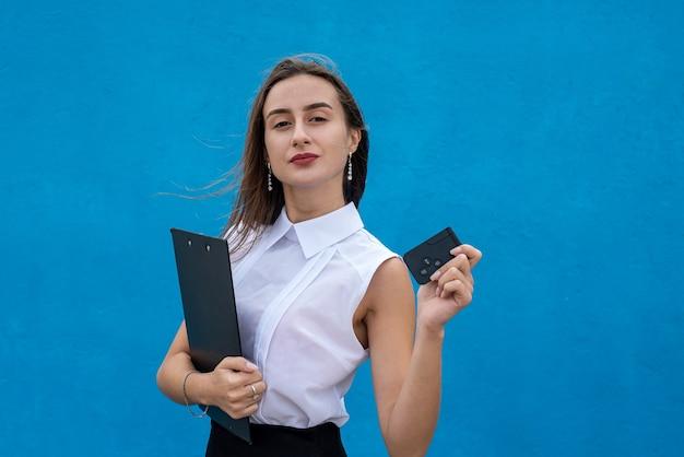 Feliz linda vendedora com um carro de chaves em fundo azul