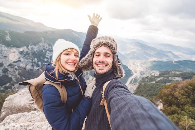 Feliz lindo casal de caminhantes tomando uma selfie no topo da montanha.
