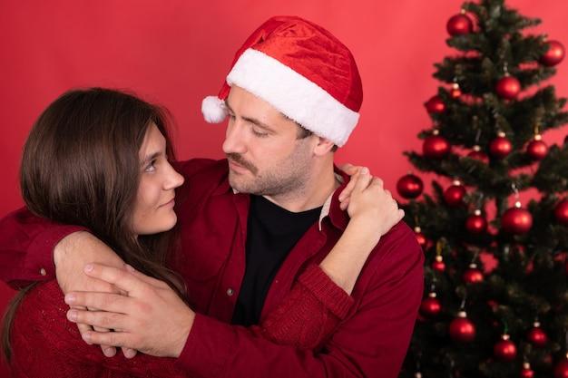 Feliz lindo casal de família comemorando o ano novo em casa na frente da árvore de natal, jovem esposa e marido abraços olham ternamente sobre fundo vermelho.