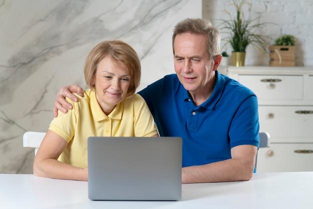 Feliz lindo casal de idosos idosos, mulher madura e lindo homem aposentado sentado em frente de