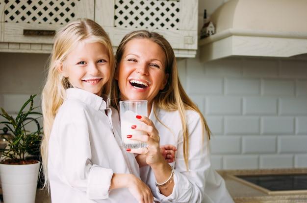 Feliz loira cabelos longos mãe e filha bebendo leite na cozinha brilhante, estilo de vida saudável