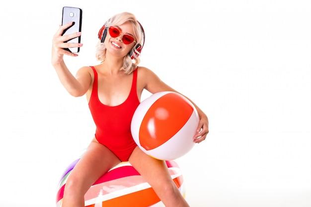 Feliz loira caucasiana fêmea encontra-se em traje de banho com colchão de borracha grande e bola colorida, fones de ouvido e sorrisos isolados