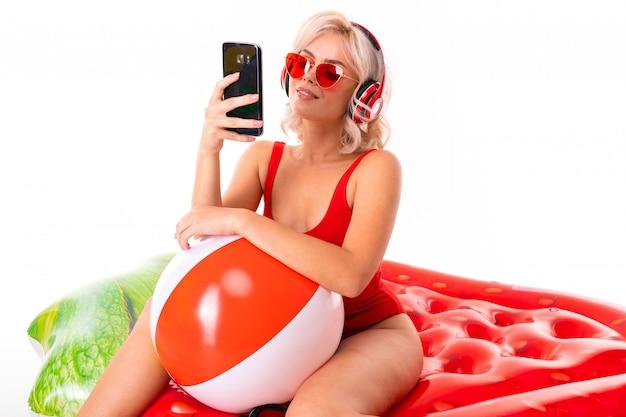 Feliz loira caucasiana feminina fica de maiô com colchão de borracha grande, telefone, fones de ouvido, fazer selfie e sorrisos isolados