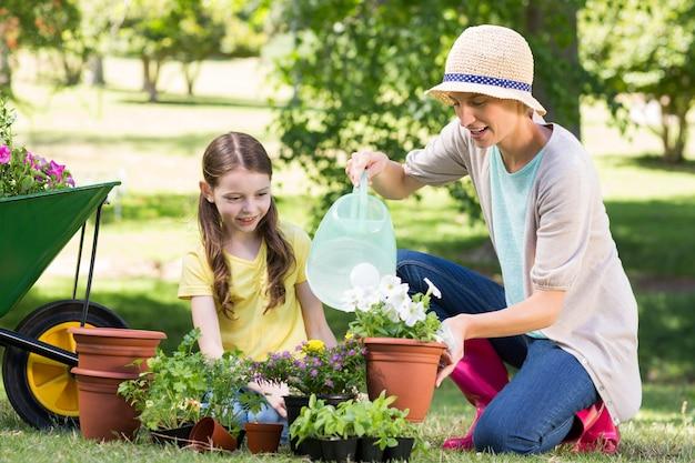 Feliz loira e sua filha em jardinagem