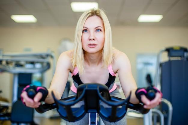 Feliz loira fazendo ciclismo indoor em um clube de fitness
