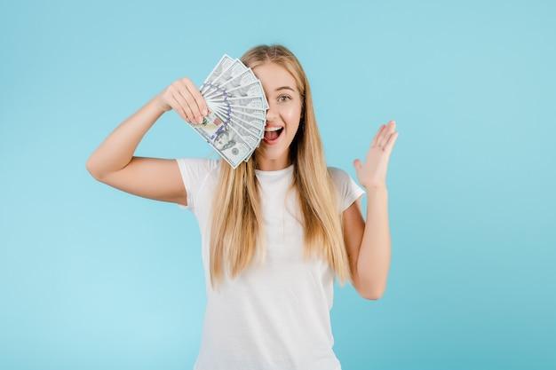 Feliz loira jovem com dinheiro dólar na mão isolada sobre azul
