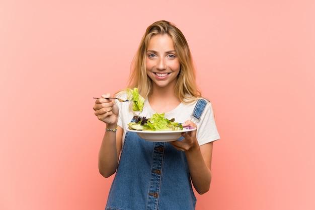 Feliz loira jovem com salada sobre parede rosa isolada