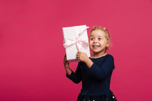 Feliz loira jovem segurando a caixa de presente e se alegra
