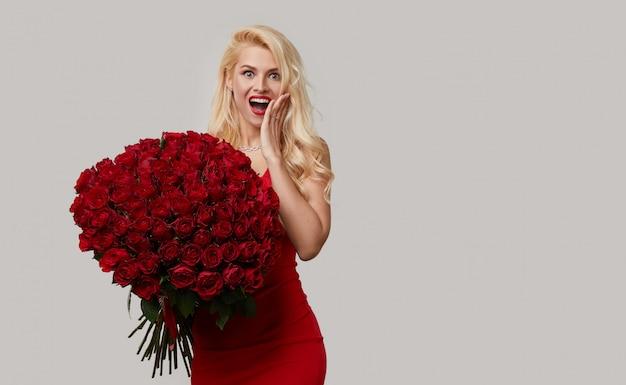 Feliz loira jovem segurando um grande buquê de rosas vermelhas como um presente para 8 de março ou dia dos namorados. ela aponta para o anel de noivado no dedo.
