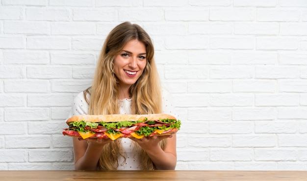 Feliz loira jovem segurando um sanduíche grande