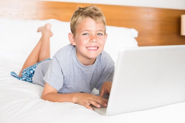 Feliz, loiro, menino, mentindo cama, usando computador portátil
