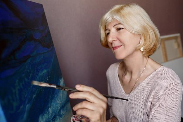 Feliz madura pintura feminina em tela em casa