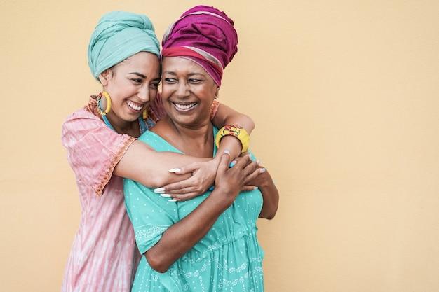 Feliz mãe africana e filha se abraçando - foco na mulher idosa