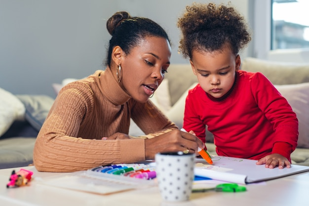 Feliz mãe afro-americana, ajudando a filha na coloração
