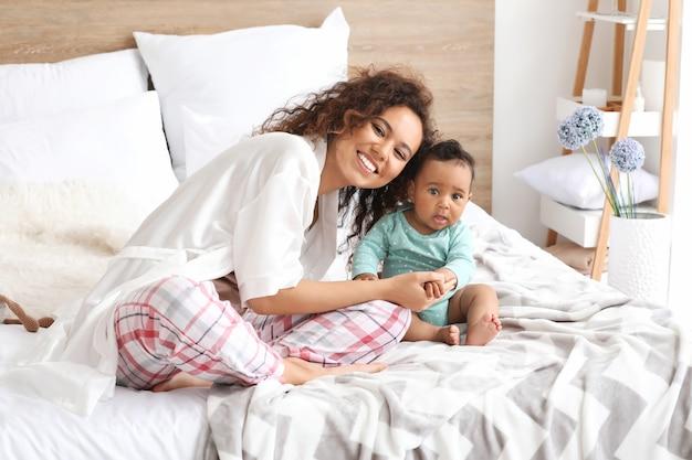 Feliz mãe afro-americana com um lindo bebezinho no quarto