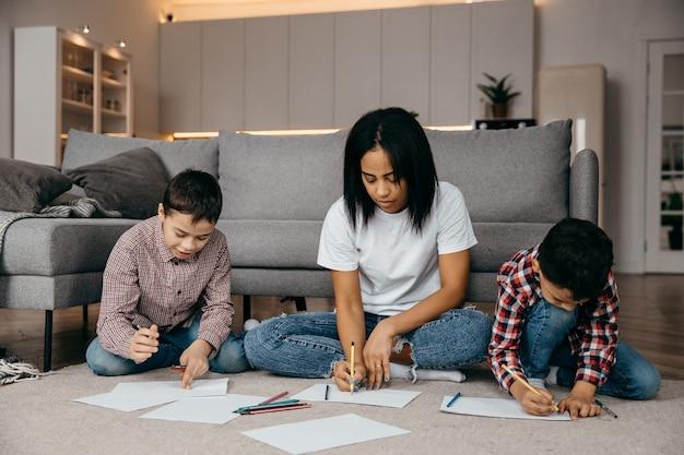 Feliz mãe afro-americana ensinando seus filhos a desenhar com lápis conceito do dia das mães