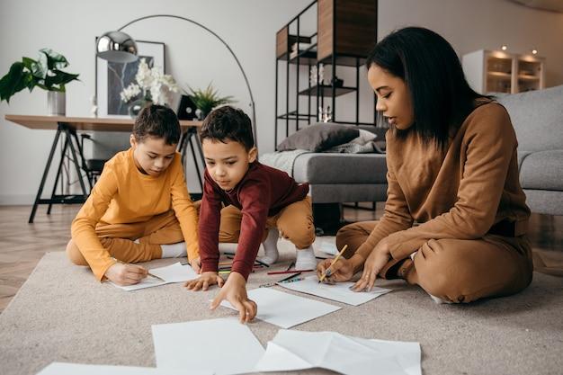 Feliz mãe afro-americana ensinando seus filhos a desenhar com lápis. conceito do dia das mães.