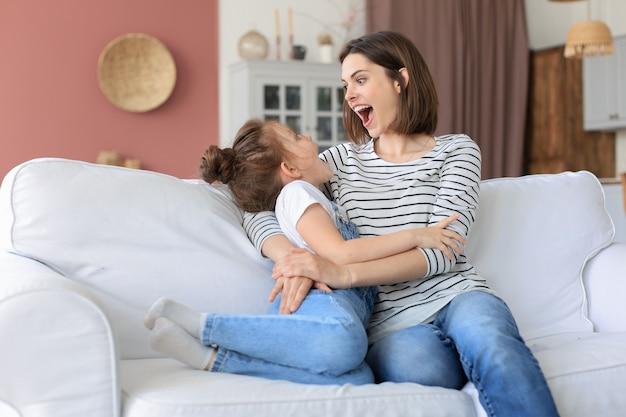 Feliz mãe amorosa abraçando a filha, passar algum tempo juntos em casa.