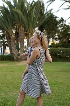 Feliz mãe amorosa e filho brincando e se abraçando. família anda perto das palmas das mãos. hotel de praia na turquia. horário de verão juntos, luz do sol. feliz dia das mães.