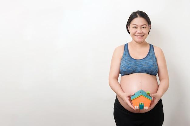 Feliz mãe asiática grávida no rosto sorridente segurando e mostrar o cofrinho em forma de casa, isolado no fundo branco, conceito de gravidez