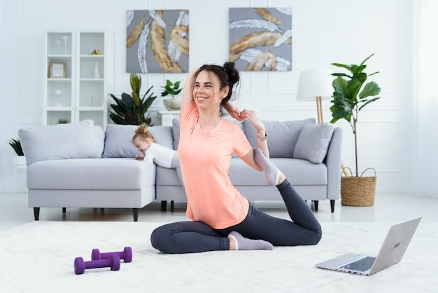 Feliz mãe calma fazendo exercícios matinais em pose de ioga, enquanto sua filha brincando em casa.