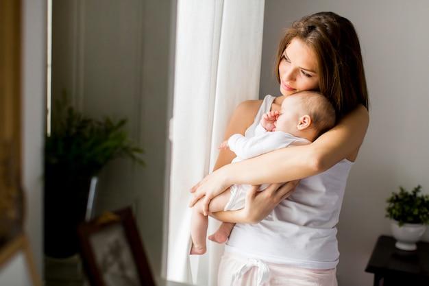 Feliz, mãe, com, bebê recem nascido, menina, por, janela