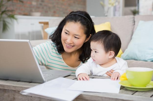 Feliz mãe com filha bebê usando laptop na sala de estar