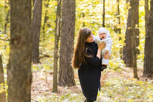 Feliz mãe e bebê ao ar livre no parque outono.