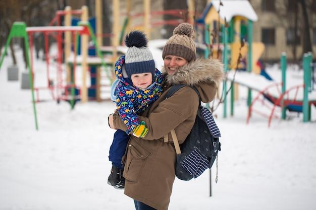 Feliz mãe e bebê em winter park. família ao ar livre. mamãe alegre com seu filho