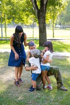 Feliz mãe e dois filhos abraçando o pai militar em uniforme de camuflagem ao ar livre. tiro vertical. conceito de reunião familiar ou retorno a casa