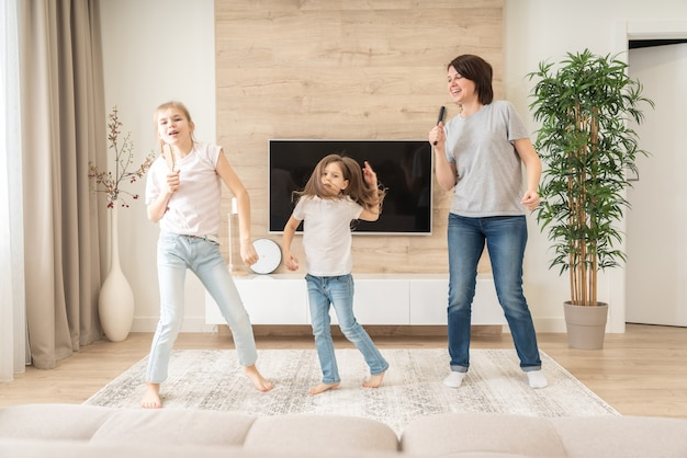 Feliz mãe e duas filhas se divertindo cantando karaokê com escovas de cabelo.