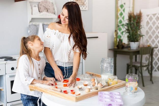 Feliz mãe e filha a cozinhar