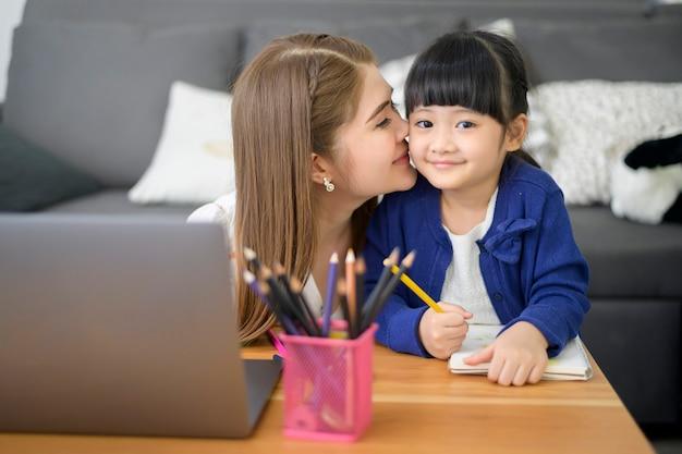 Feliz mãe e filha asiáticas estão usando laptop para estudar online através da internet em casa. conceito de e-learning durante o tempo de quarentena.
