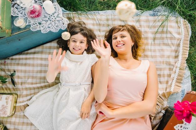 Feliz mãe e filha brincando e sorrindo enquanto estava deitado em um cobertor no verão