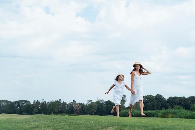 Feliz mãe e filha caminhando ao ar livre