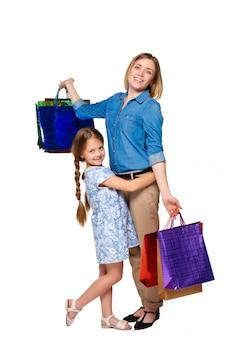 Feliz mãe e filha com sacos de compras em pé