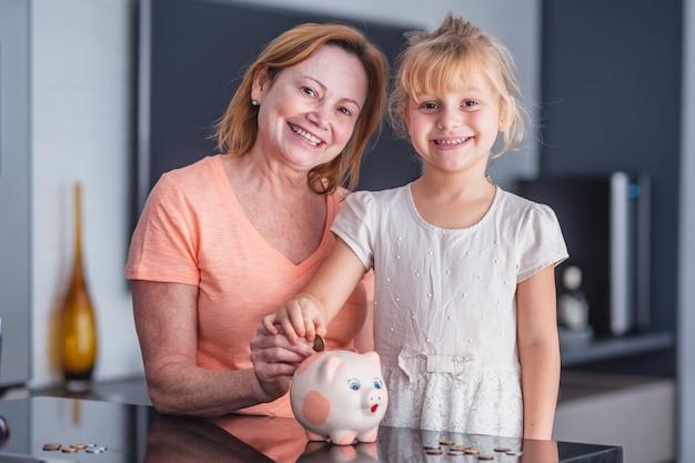 Feliz mãe e filha com um cofrinho salvando